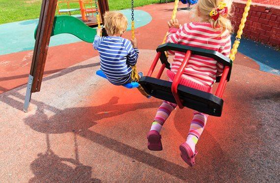 Crianças brincando sob o piso emborrachado para playground