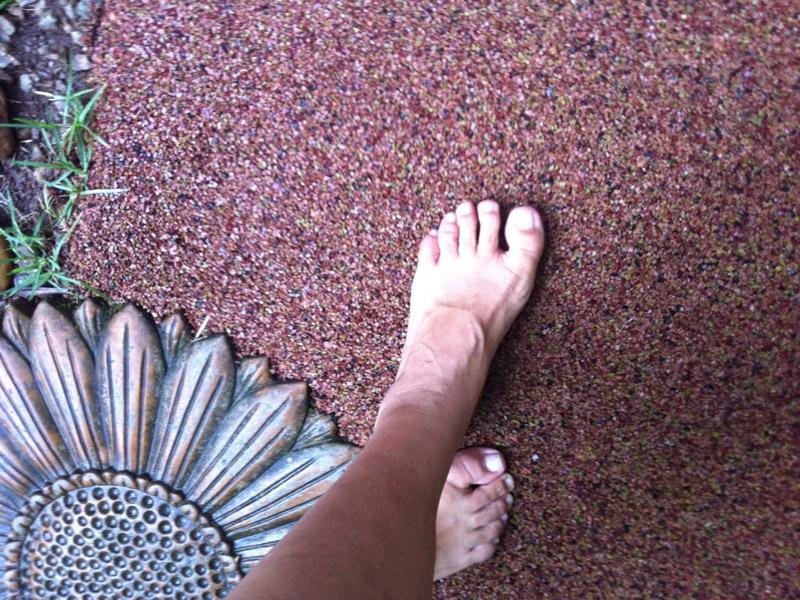 Piso drenante de borracha para jardim, decorado com flores, no detalhe mostra o pé de uma modelo descalça circulando pelo piso.