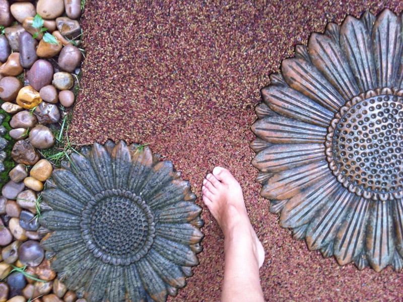 Piso drenante de borracha para jardim, decorado com flores, no detalhe mostra o pé de uma modelo descalça circulando pelo piso, foto em outro ângulo.
