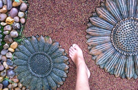 Pé de uma mulher sobre o piso drenante de borracha, aplicado em um jardim