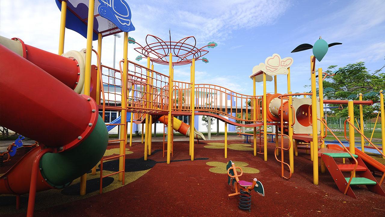 playground com piso de borracha de pneu reciclável na área externa do parquinho nas cores vermelho, amarelo e preto