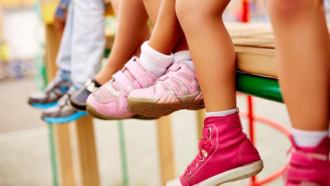 crianças sentadas em brinquedo de um playground sobre um piso de borracha seguro contra quedas