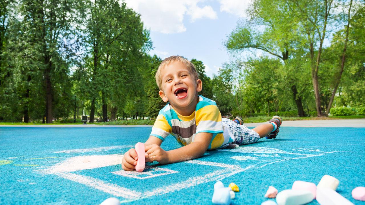 menina brincando sobre um piso de borracha azul desenhando com giz no piso