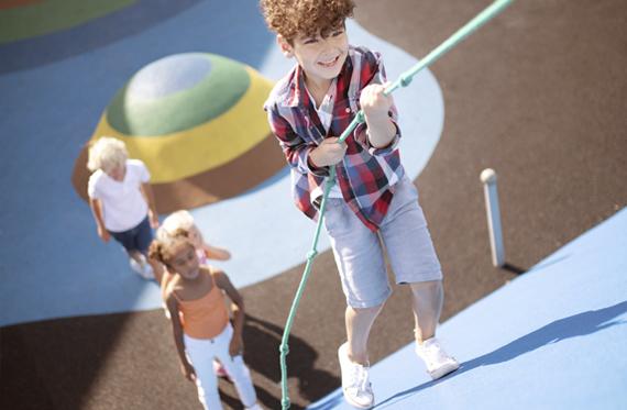 criança escalando montanha de playground revestido com piso emborrachado