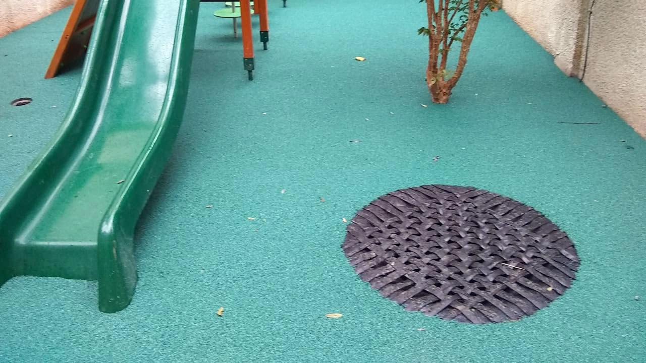 playground pequeno verde com escorregador e mini cama elástica em um espaço pequeno